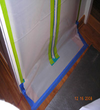 Mold remediation containment doorway properly sealed to floor.